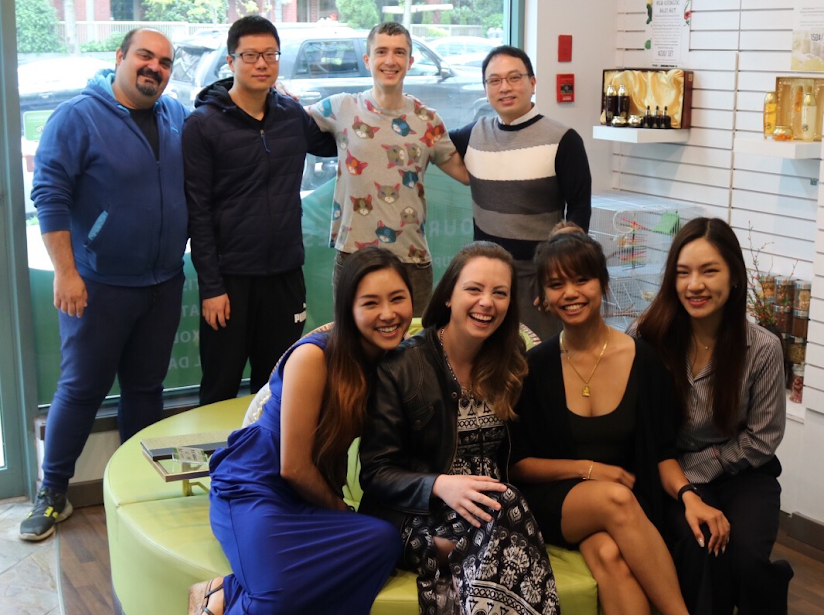 Janaina Batista smiling happily with her coworkers at the Yaletown Wellness Center